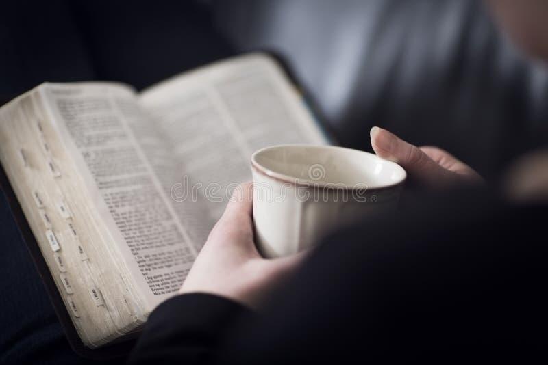 Frau las die Bibel und trinkt Tee oder Kaffee lizenzfreie stockfotografie