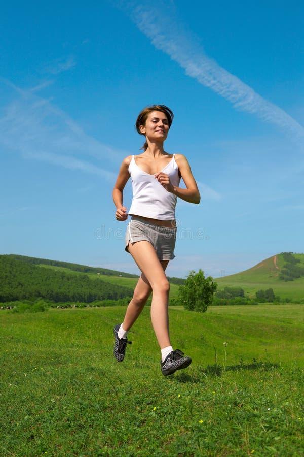 Frau laufen gelassen auf grünes Gras stockfotografie
