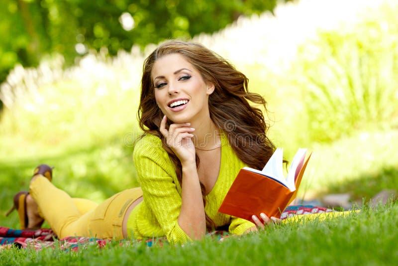 Frau legt auf grünes Feld und liest Buch. stockfotos