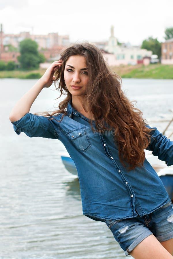 Frau lehnte sich zum Fluss auf dem Überstadthintergrund lizenzfreies stockfoto