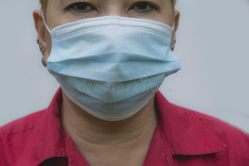 Frau leiden unter kranker und tragender Gesichtsmaske stockfoto