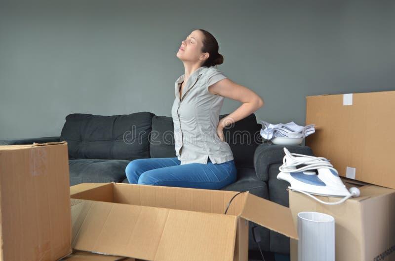 Frau leidet unter den Rückenschmerzen, die zum Auspacken von Kästen passend sind stockfoto