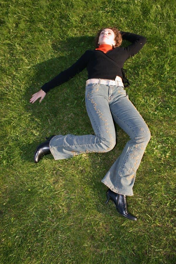 Frau liegt auf Gras lizenzfreie stockfotos