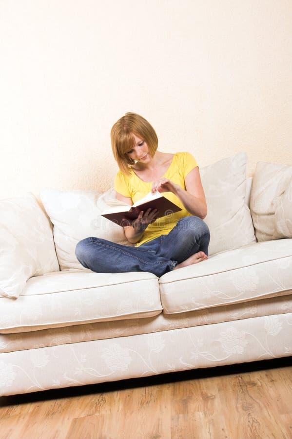 Frau liest auf einem Aufenthaltsraum stockbild