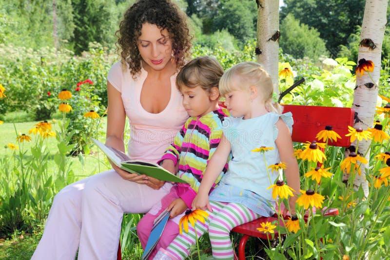 Frau liest Buch zu zwei kleinen Mädchen im Garten lizenzfreie stockbilder