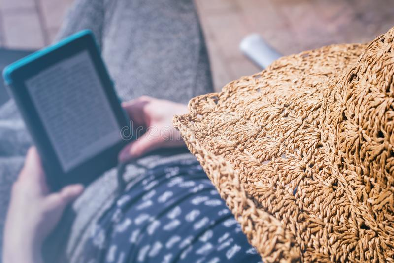 Frau liest im Sonnenschein auf ihrem eBook Leser lizenzfreies stockfoto