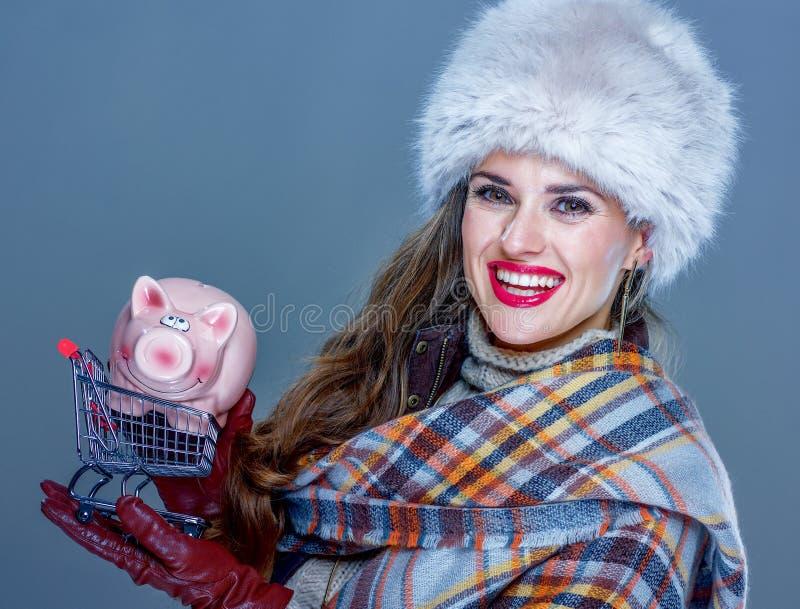 Frau lokalisiert auf kalter blauer haltener Einkaufslaufkatze mit piggy stockfotos