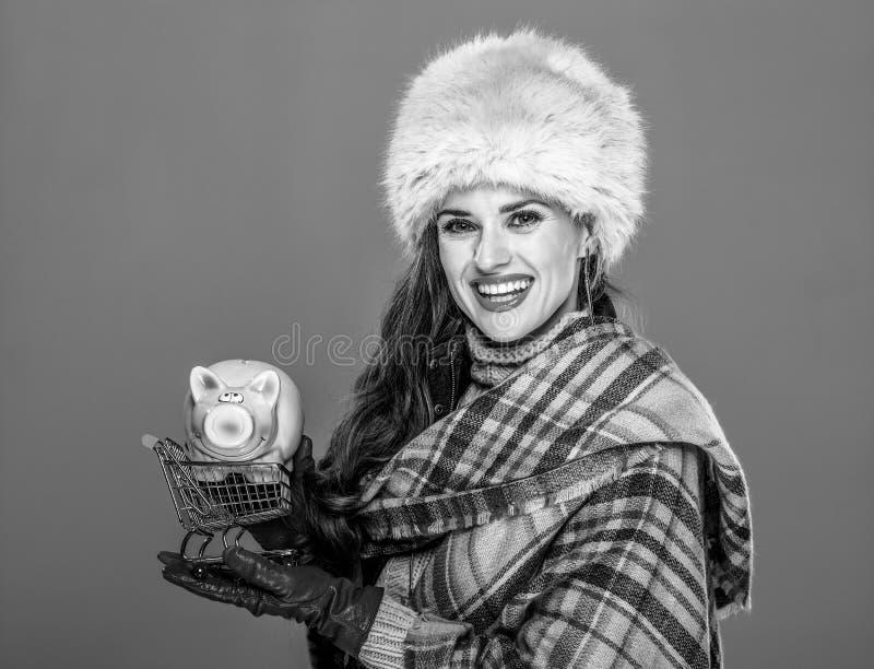 Frau lokalisiert auf kalter blauer haltener Einkaufslaufkatze mit piggy lizenzfreies stockfoto