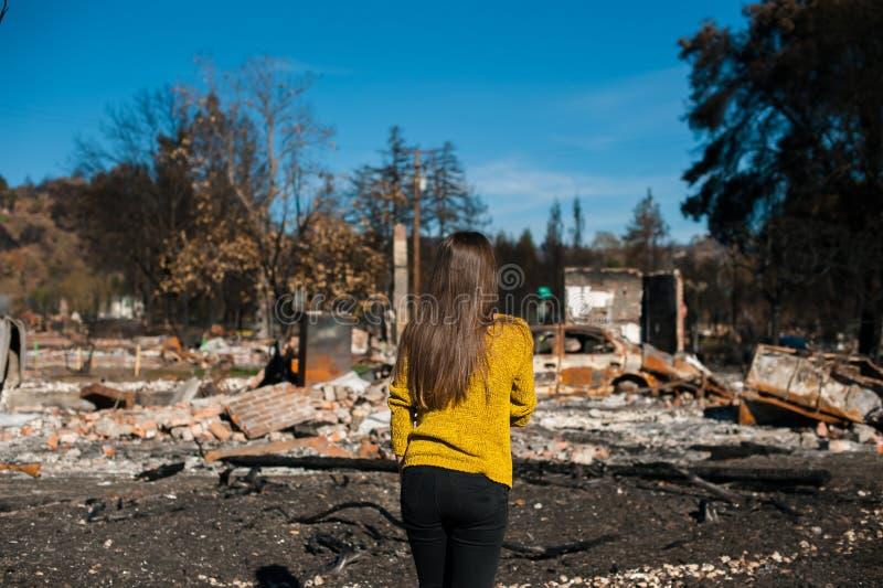 Frau lookinh an ihrem gebrannten Haus nach Feuerunfall stockfotos