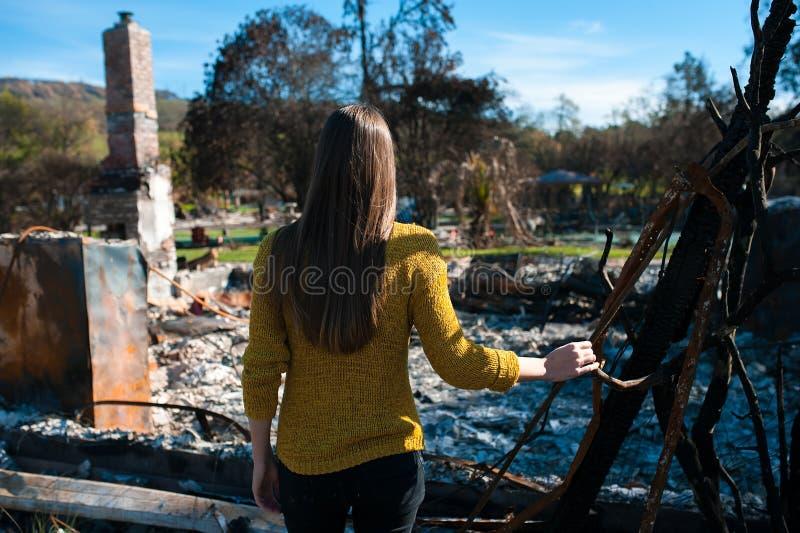 Frau lookinh an ihrem gebrannten Haus nach Feuerunfall stockbild