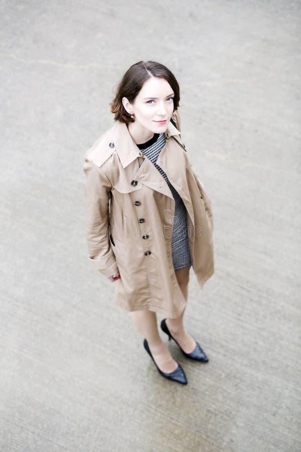 Frau am losen beige Mantel auf graulichem Quadrat stockfoto