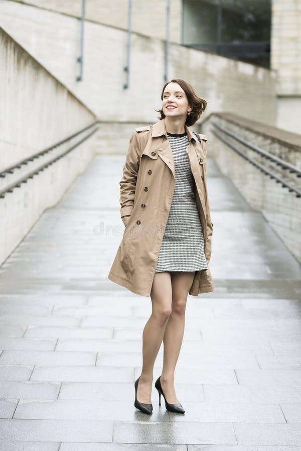 Frau am losen beige Mantel in der guten Laune lizenzfreie stockfotos