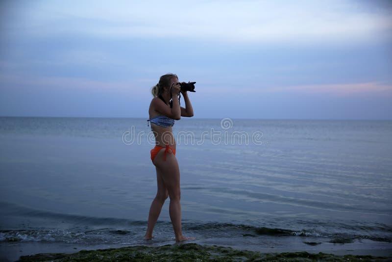Frau machen ein Foto auf der Seeküste stockbild