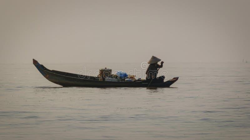 Frau macht ihren Übergang den See in ihrem sich hin- und herbewegenden Küchenboot Die meisten Häuser haben nicht Damen der Anlage lizenzfreie stockfotos