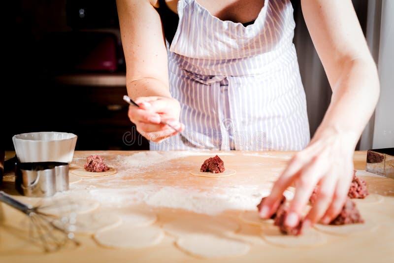 Frau macht Mehlklöße zu Hause auf Küchentisch, Abschluss oben stockbild