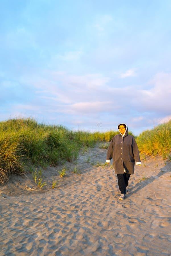 Frau macht ruhigen entspannten Spaziergang entlang Strand stockbilder