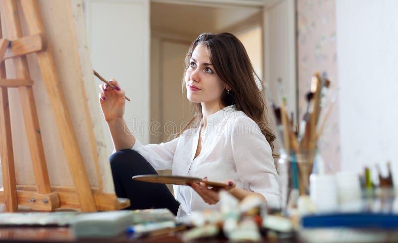 Frau malt Bild auf Segeltuch lizenzfreies stockbild