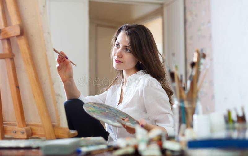 Frau malt Bild auf Segeltuch in ihrem Studio lizenzfreie stockfotografie