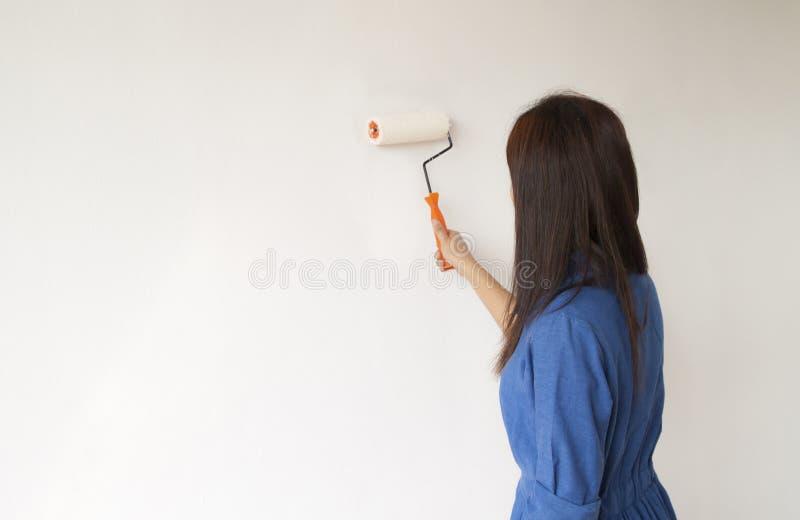 Frau malt die Wand lizenzfreie stockfotografie