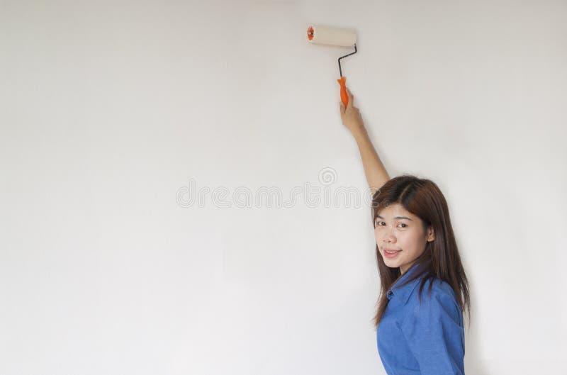 Frau malt die Wand lizenzfreie stockfotos