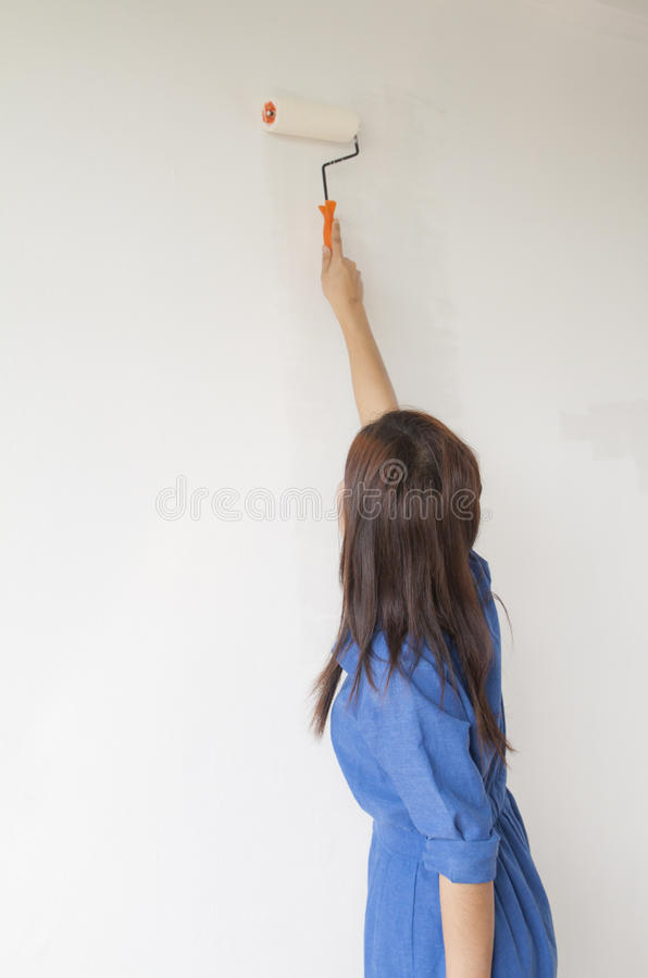 Frau malt die Wand stockbild