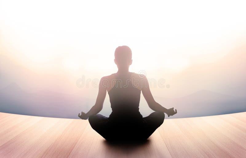 Frau meditierte am Morgen und an den Strahlen des Lichtes auf Landschaft stockbild