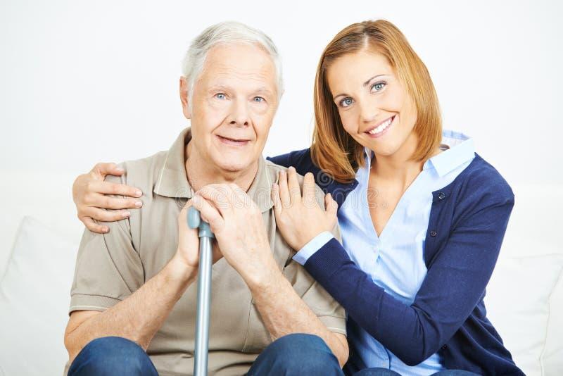 Frau mit älterem Mann im Pflegeheim lizenzfreie stockbilder
