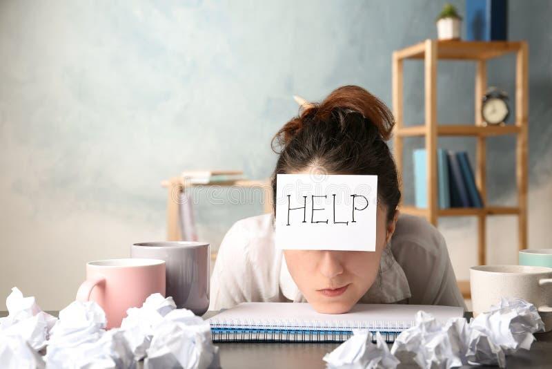 Frau mit Anmerkung HILFE auf Stirn am Arbeitsplatz lizenzfreies stockfoto