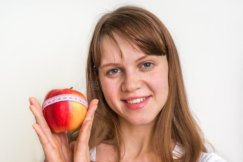 Frau mit Apfel und Maßband auf Weiß lizenzfreie stockbilder