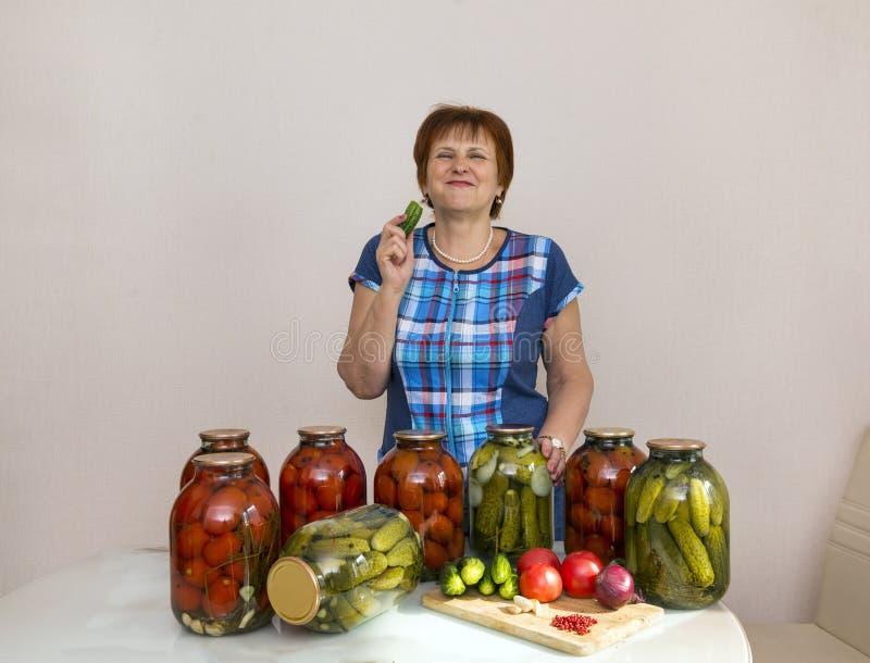 Frau mit in Büchsen konservierten Essiggurkengurken und Tomaten, in Essig eingelegtes vegeta lizenzfreies stockbild