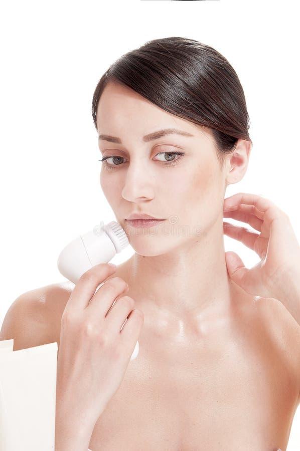 Frau mit Bürste für tief Reinigungsgesichtsbehandlung. stockfotografie