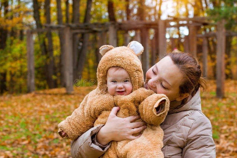 Frau mit Baby in den Armen, werfend in Herbst Park auf lizenzfreie stockfotografie