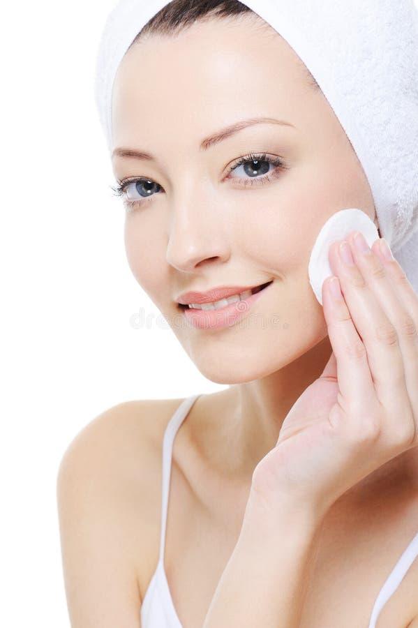 Frau mit Baumwollputzlappenreinigung ihr Gesicht lizenzfreies stockbild