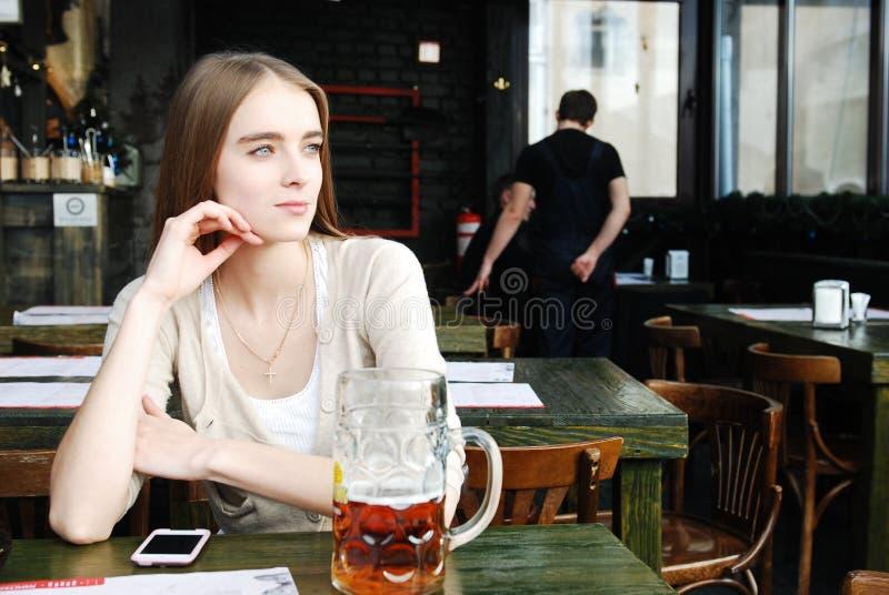Frau mit Becher Getränkbier am Kaffee lizenzfreies stockbild