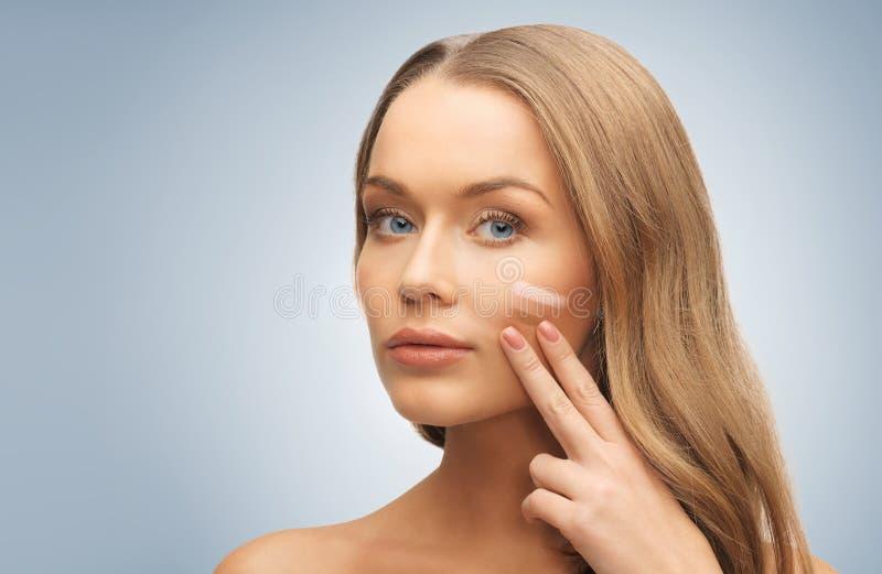 Frau mit blassem und dunklem Grundlagenton auf Gesicht lizenzfreie stockfotos