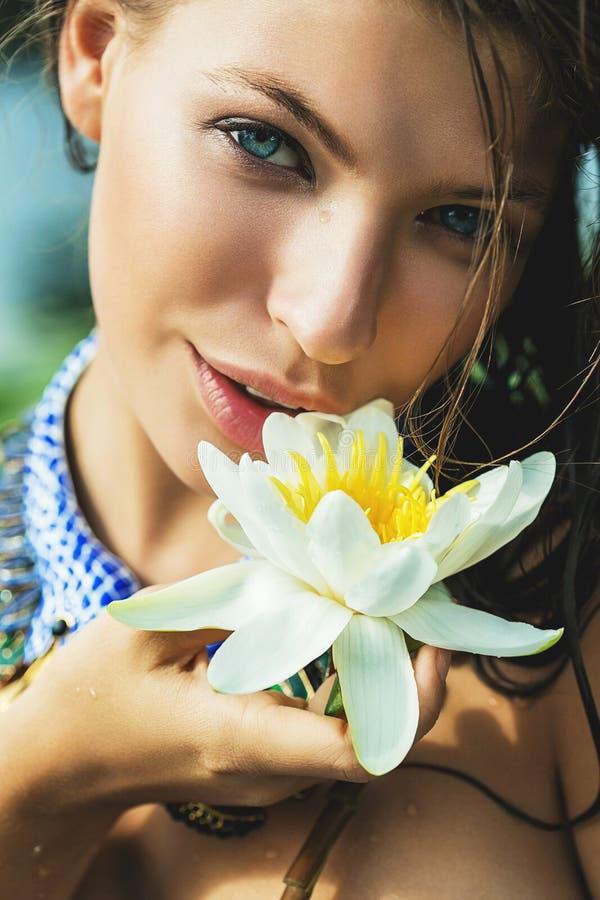 Frau mit blauen Augen mit Wildwasserlilie in der Hand lizenzfreie stockfotografie