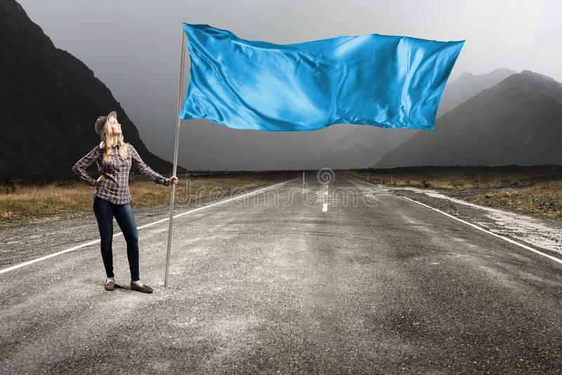 Frau mit blauer wellenartig bewegender Flagge stockfotos