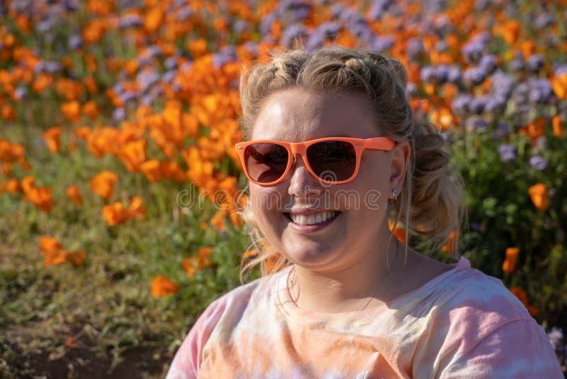 Frau mit blonden umsponnenen Haar- und Sonnenbrillehaltungen auf einem Mohnblumengebiet w?hrend einer Superbl?te Konzept f?r Fr?h stockfoto