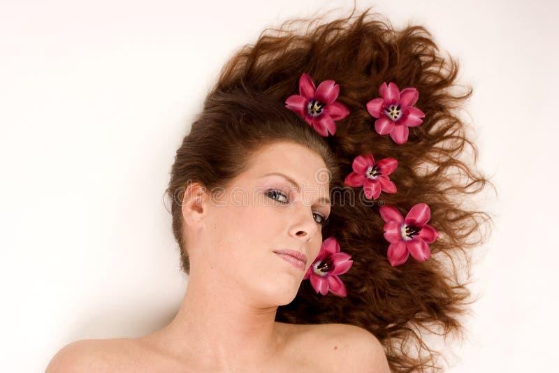 Frau mit Blumen in ihrem Haar lizenzfreie stockfotos