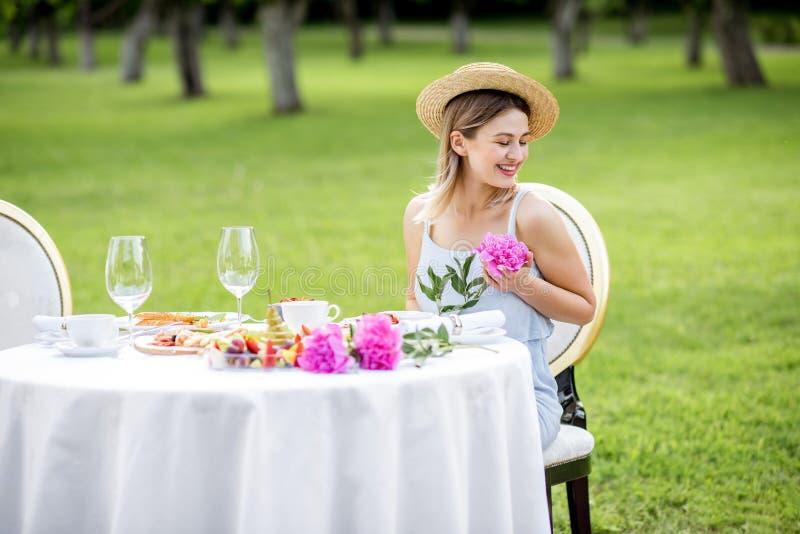 Frau mit Blumen während des Frühstücks draußen stockfotografie