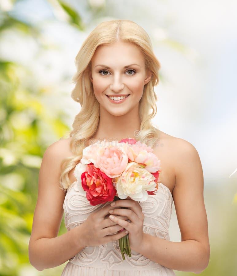 Frau mit Blumenstrauß von Blumen lizenzfreie stockfotografie