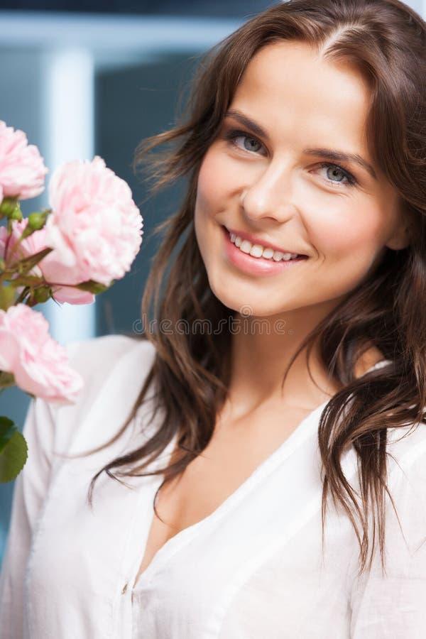 Frau mit Blumenstrauß von Blumen zu Hause lizenzfreie stockbilder