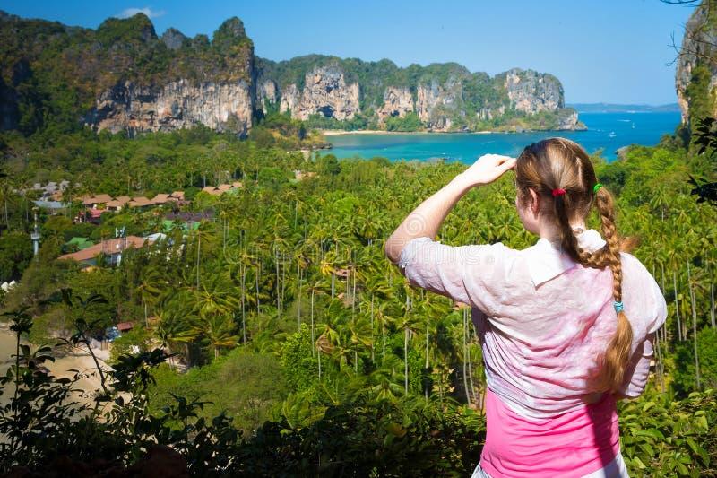 Frau mit Borten im rosa Hemd steht an der rechten Seite auf die Oberseite des Berges und passt über die Dschungel und sandig auf lizenzfreies stockbild