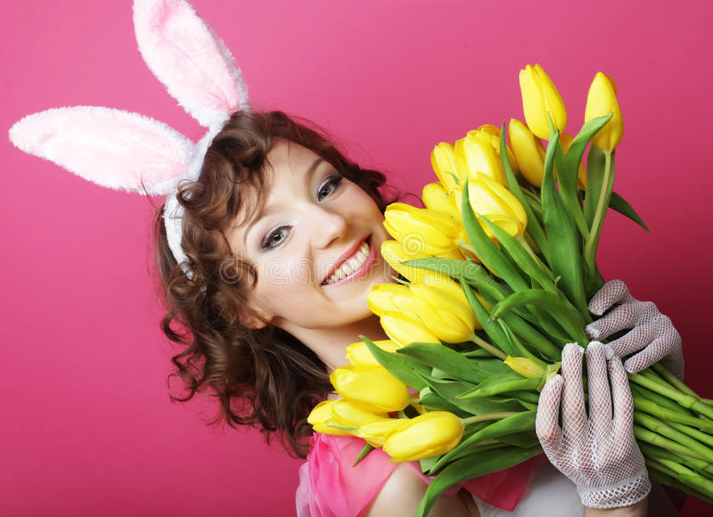 Frau mit Bunny Ears, der gelbe Tulpen hält lizenzfreie stockbilder