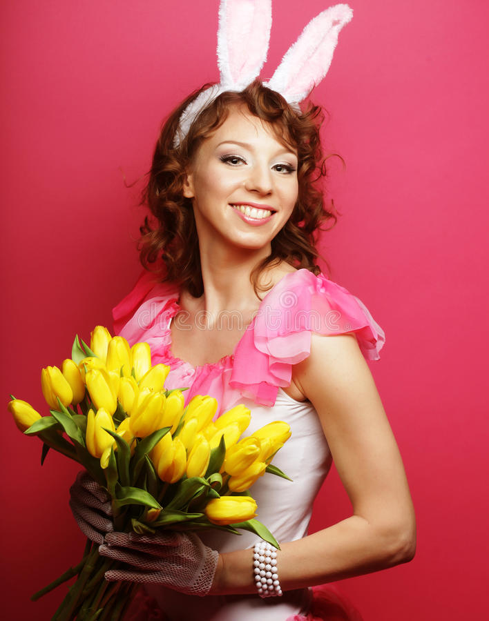 Frau mit Bunny Ears, der gelbe Tulpen hält lizenzfreies stockfoto