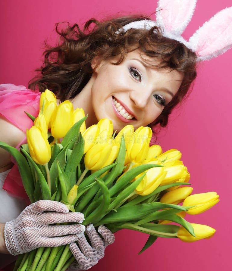 Frau mit Bunny Ears, der gelbe Tulpen hält lizenzfreies stockbild