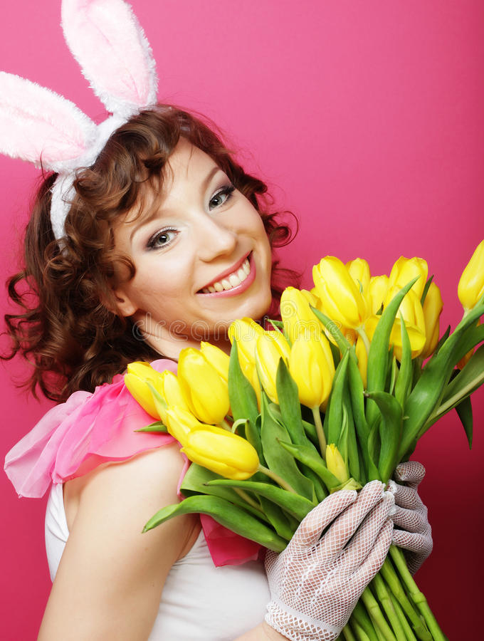 Frau mit Bunny Ears, der gelbe Tulpen hält stockbild