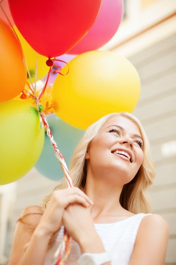 Frau mit bunten Ballonen stockbild