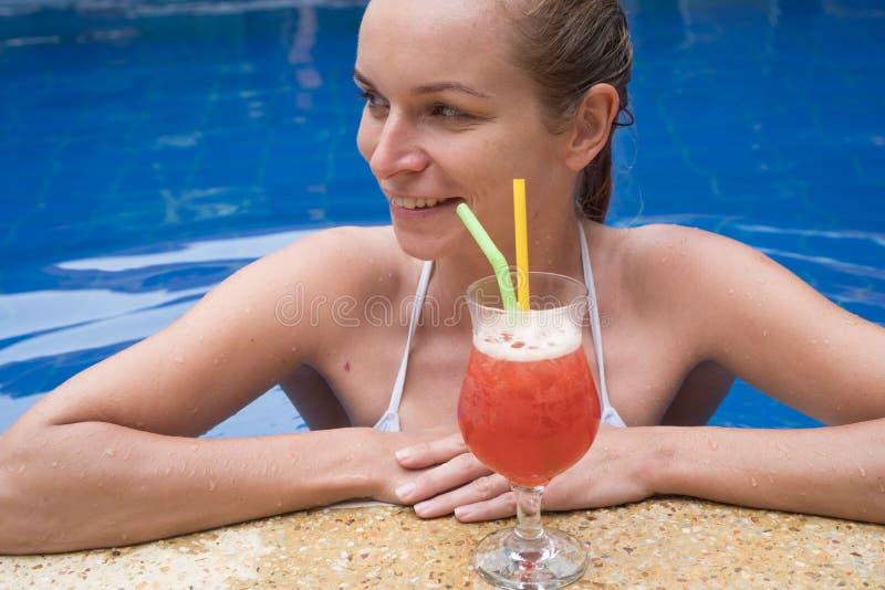 Frau mit Cocktail im Pool stockfotos