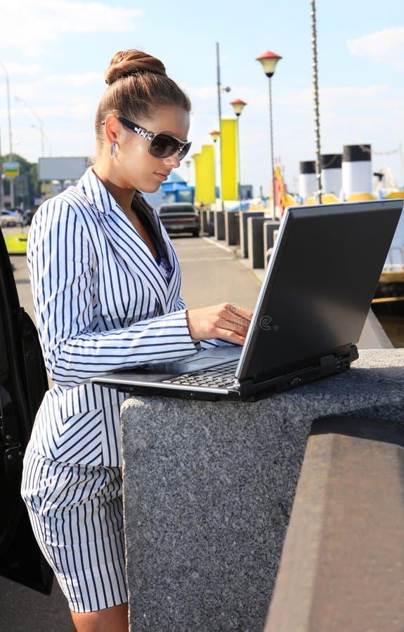 Frau mit Computer auf Kai lizenzfreies stockbild